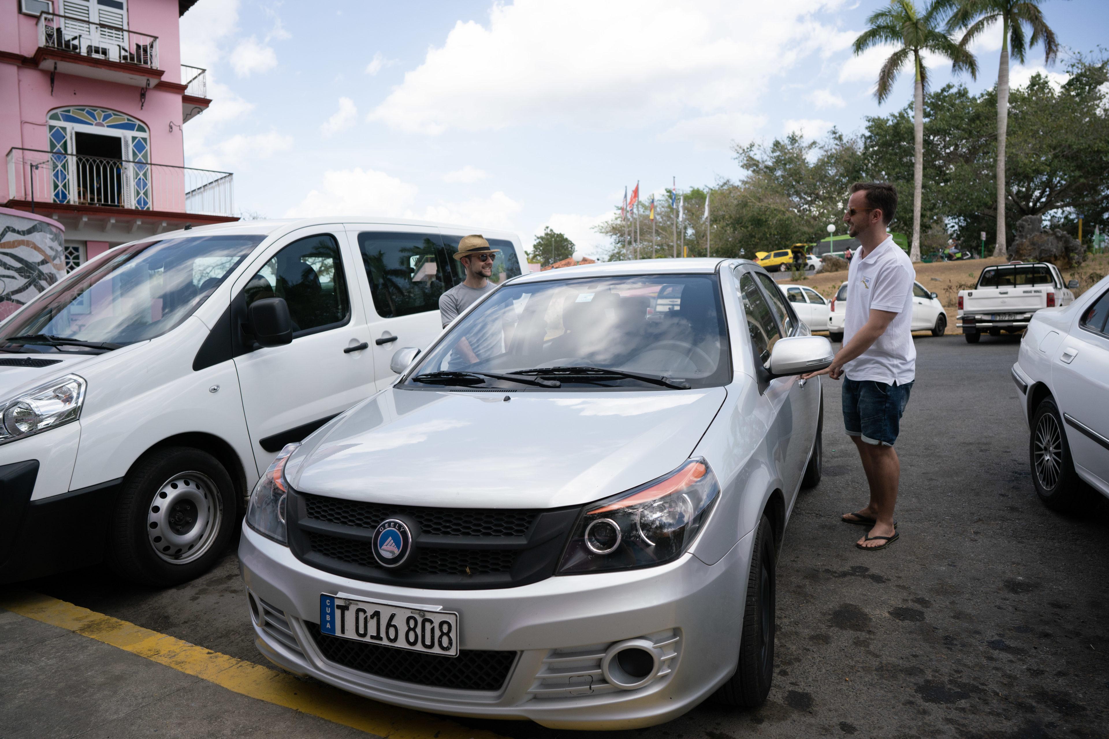 Zwei Kuba-Reisende öffnen ihren Mietwagen