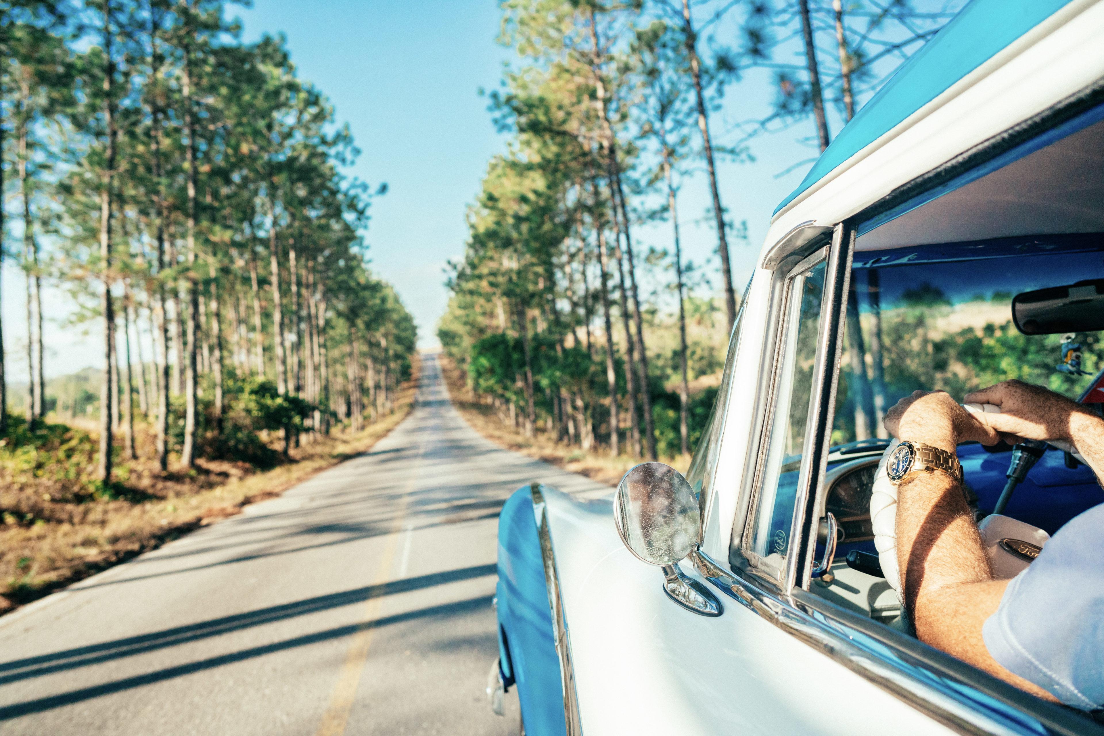 Reisende fahren mit ihren Mietwagen durch Kuba