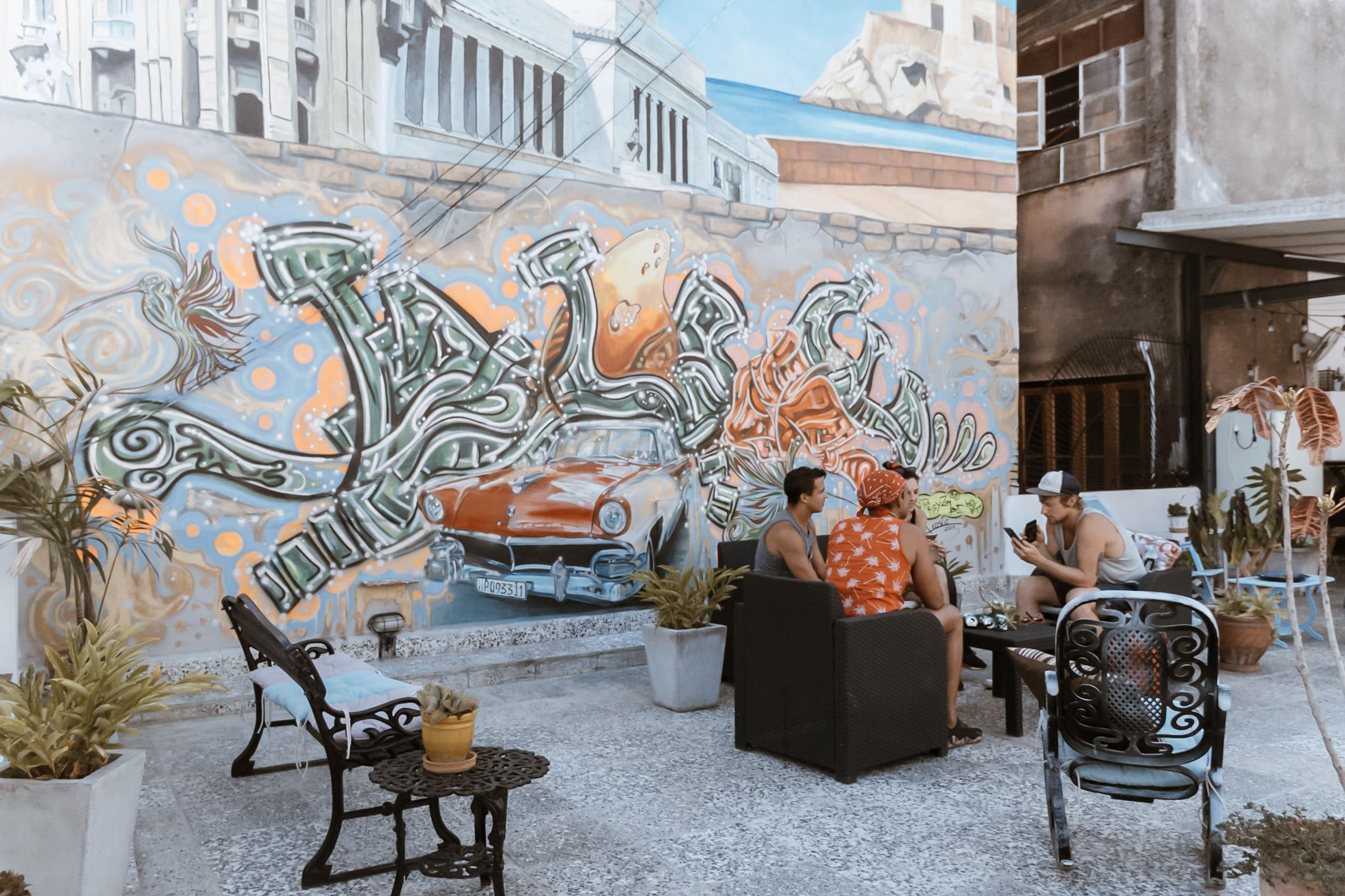 Menschen sitzen vor einem Graffiti auf einer Dachterrasse in Kuba