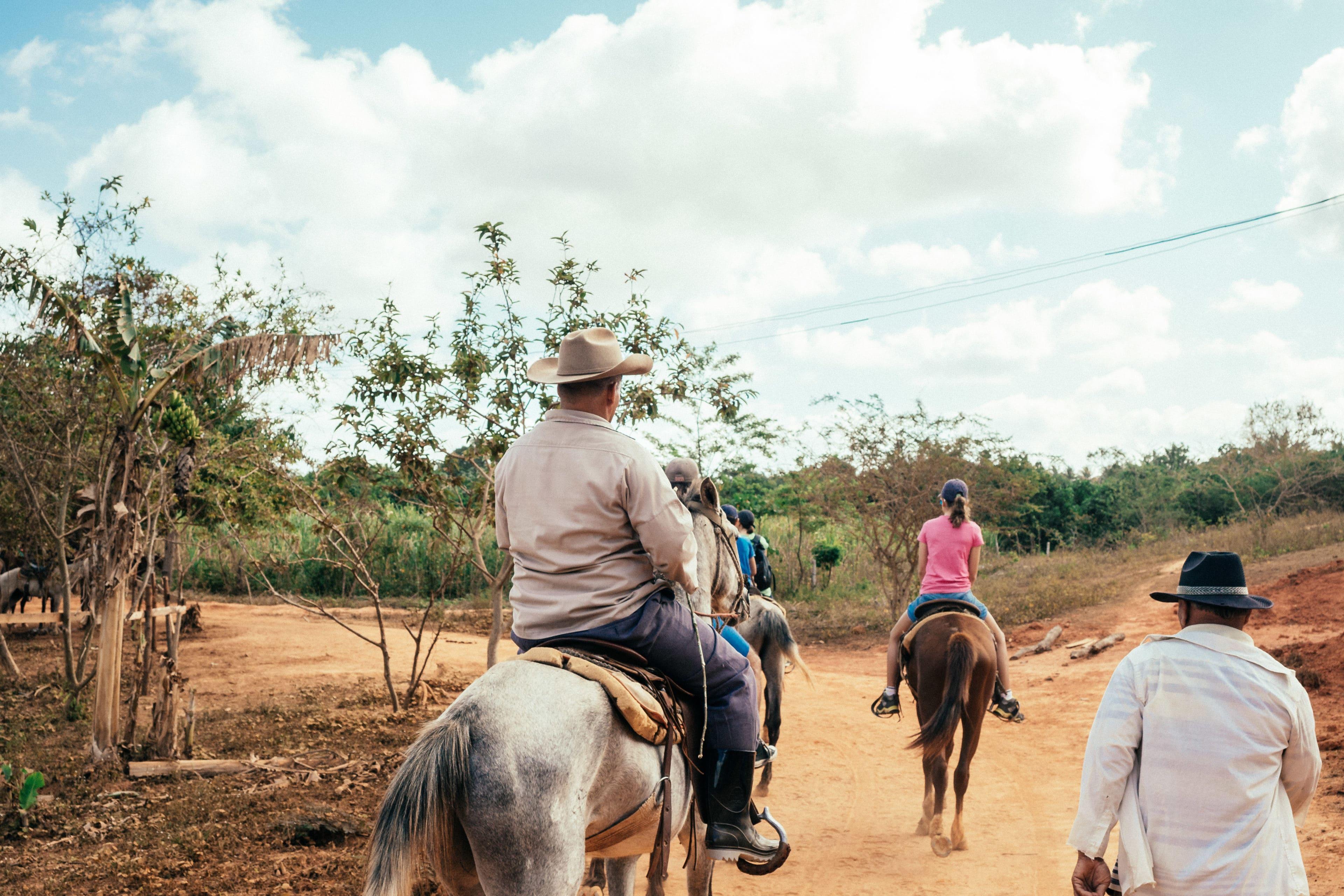 Kuba-Reisende reiten durch die Tabakfelder im idyllischen Tal von Viñales