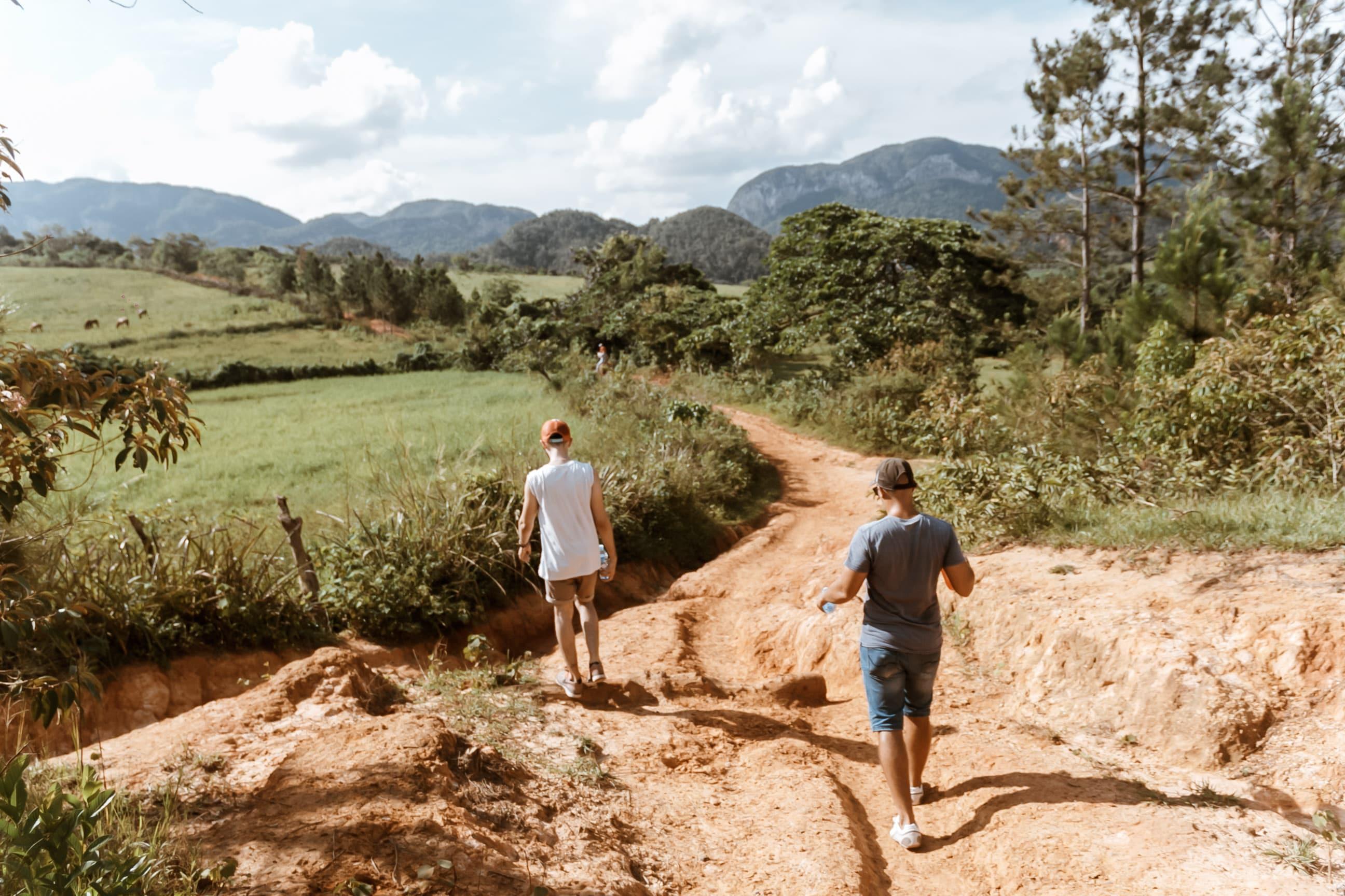 Zwei Reisende wandern durch kubanische Berge in Viñales