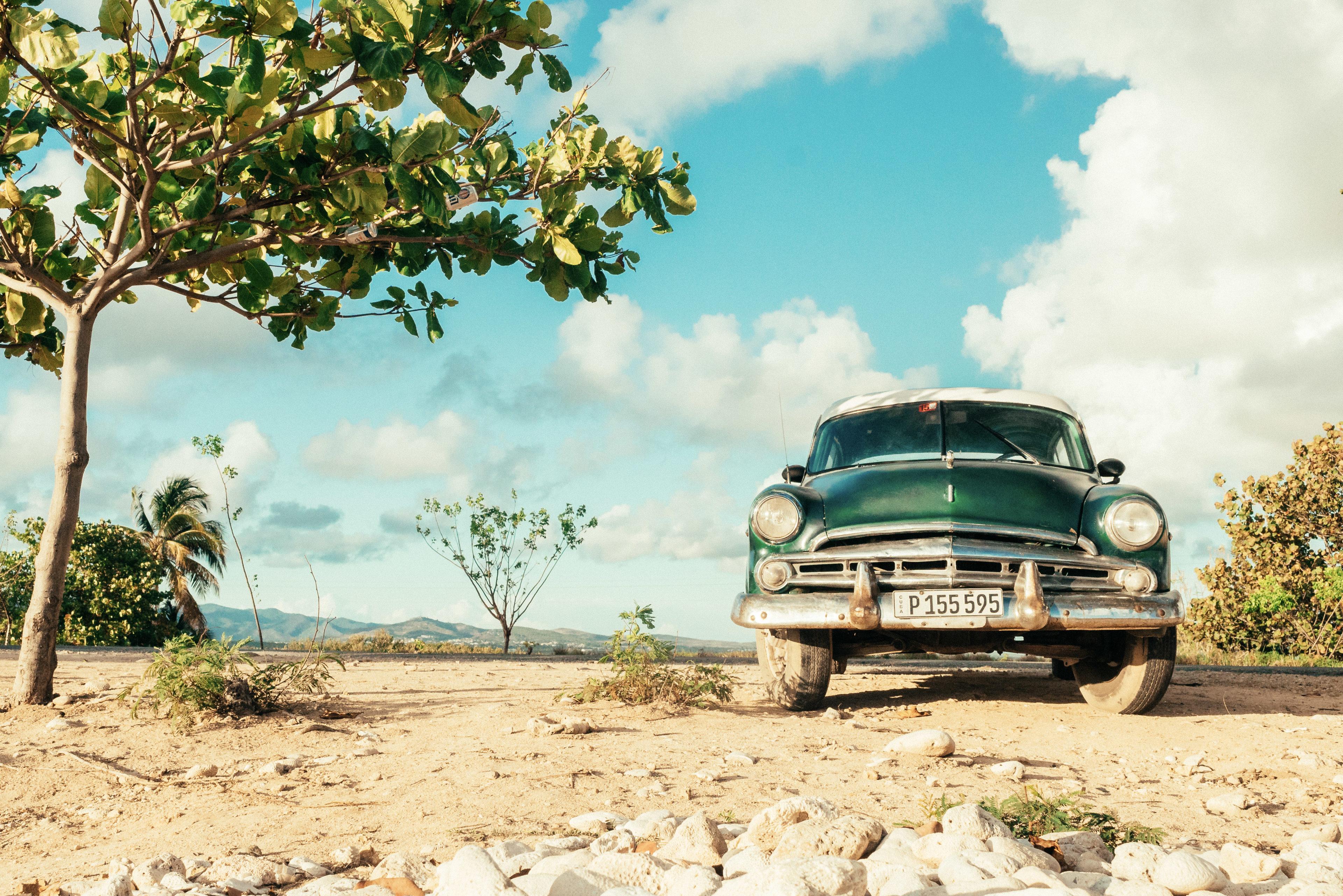 Ein Oldtimer steht in einer steppenartigen Landschaft in Kuba