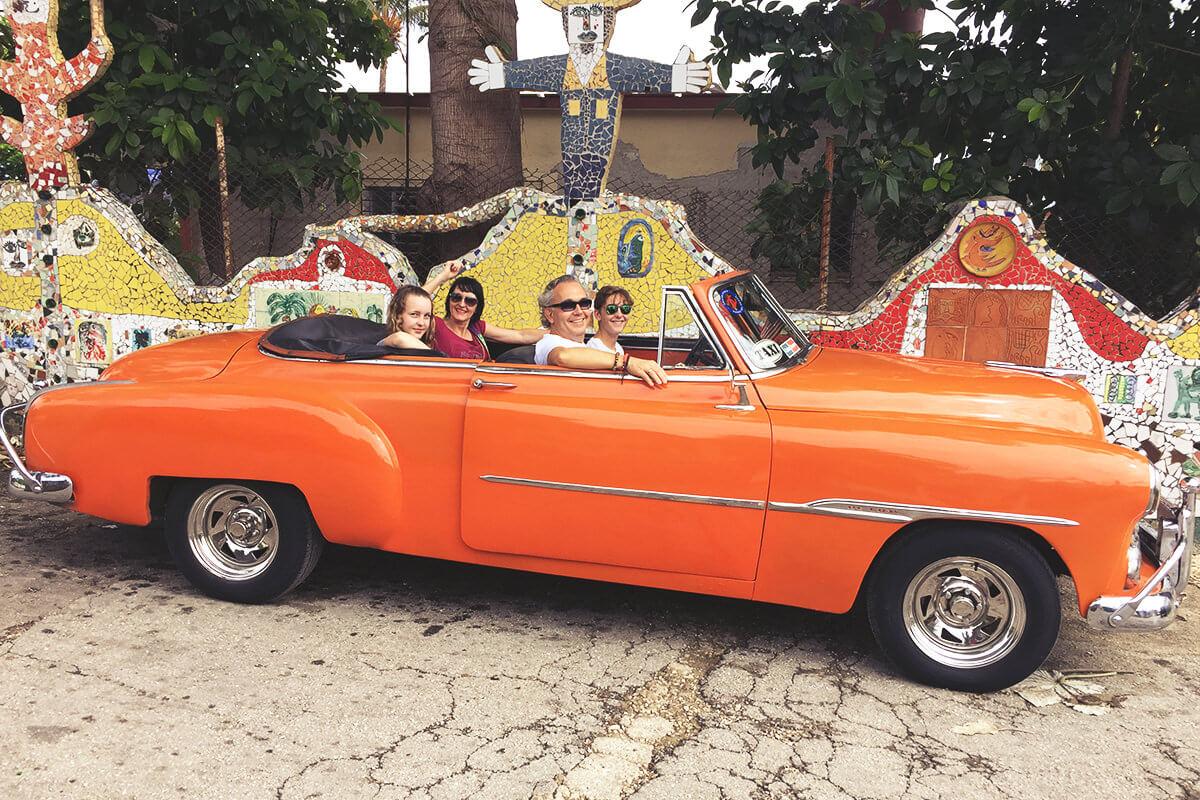 Oldtimer mit Familie vor Mosaik-Kunst in Kuba
