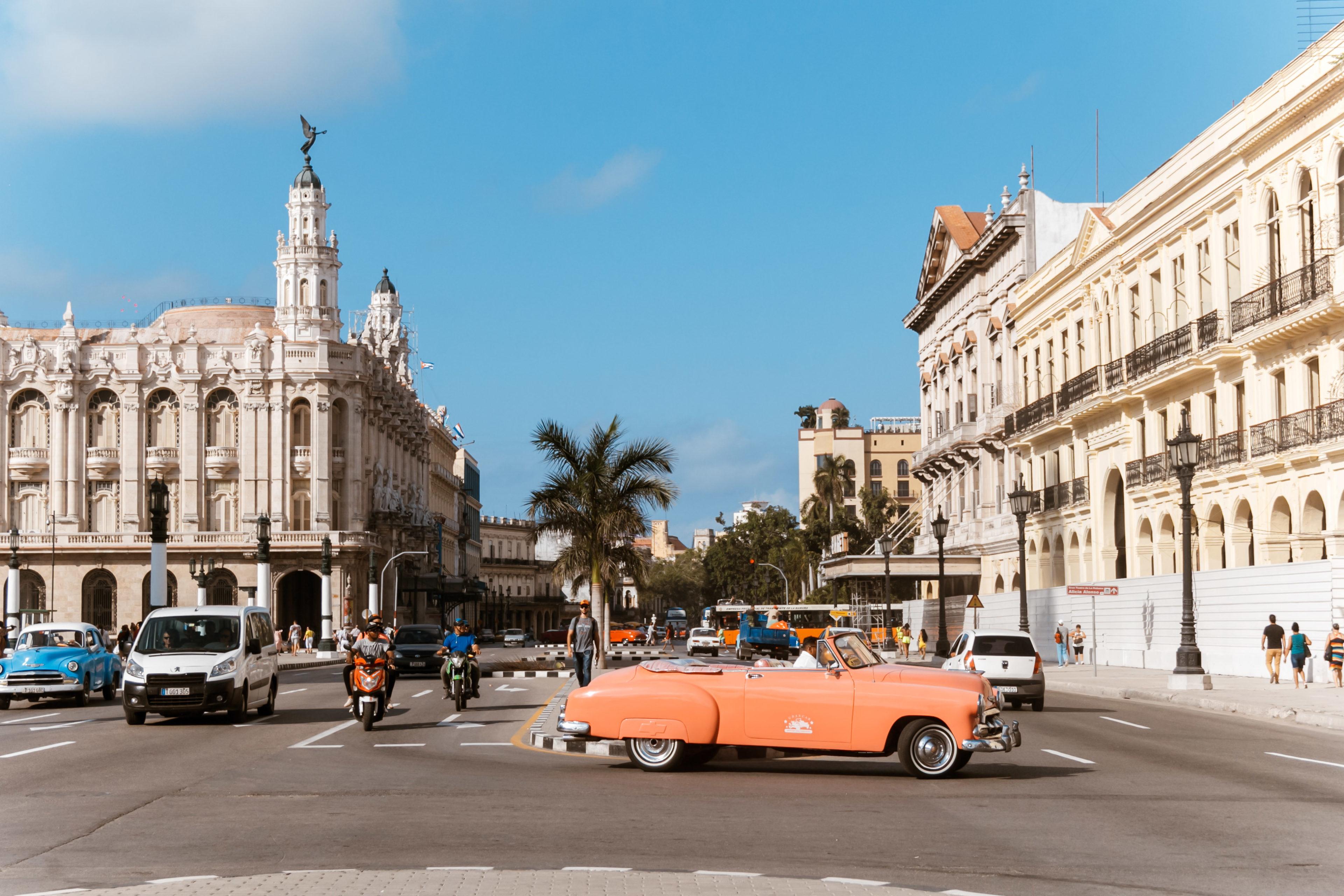 Ein roter Oldtimer fährt durch Havanna