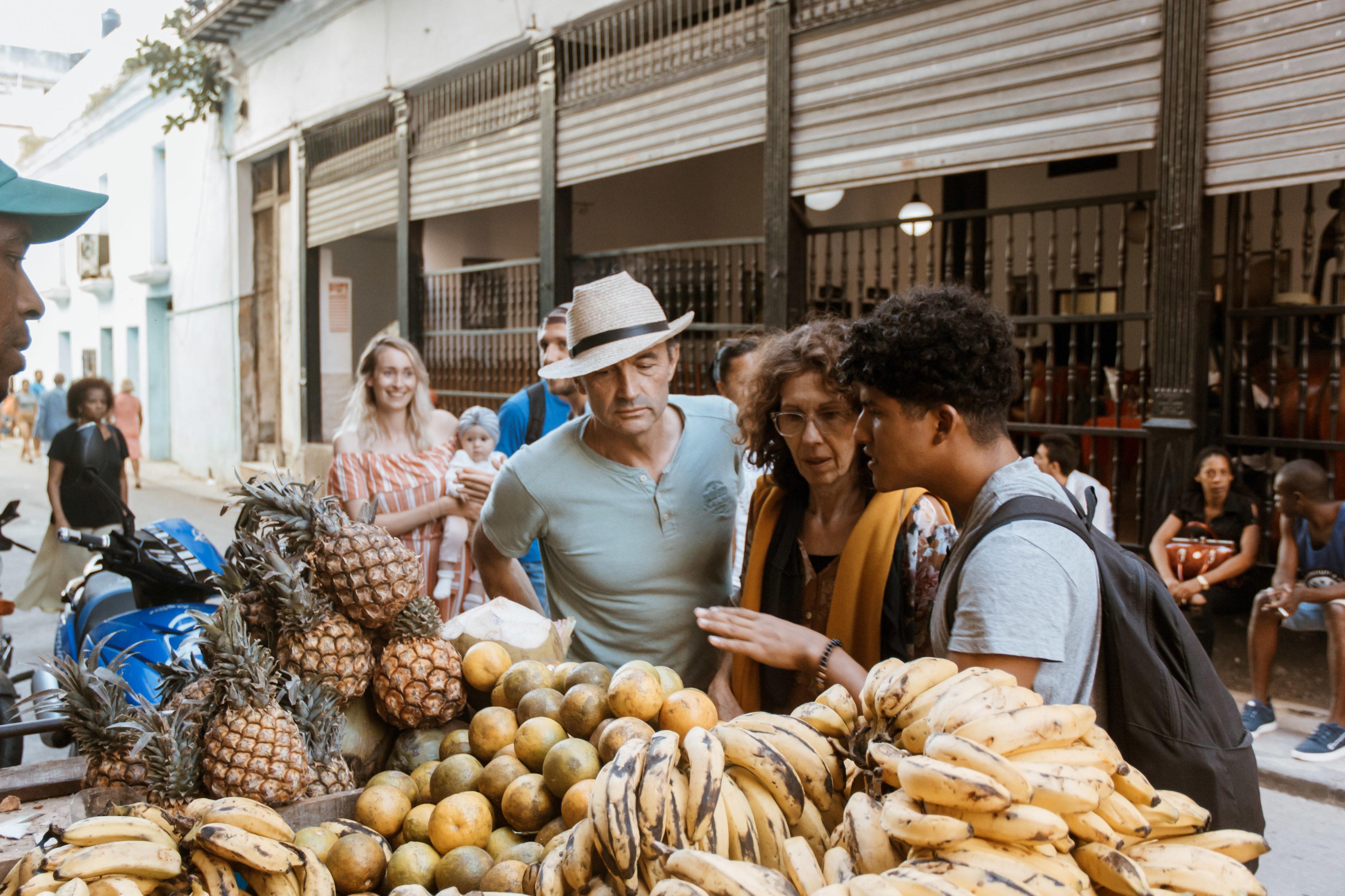 Reisende kaufen frisches Obst an einem Straßenstand in Havanna