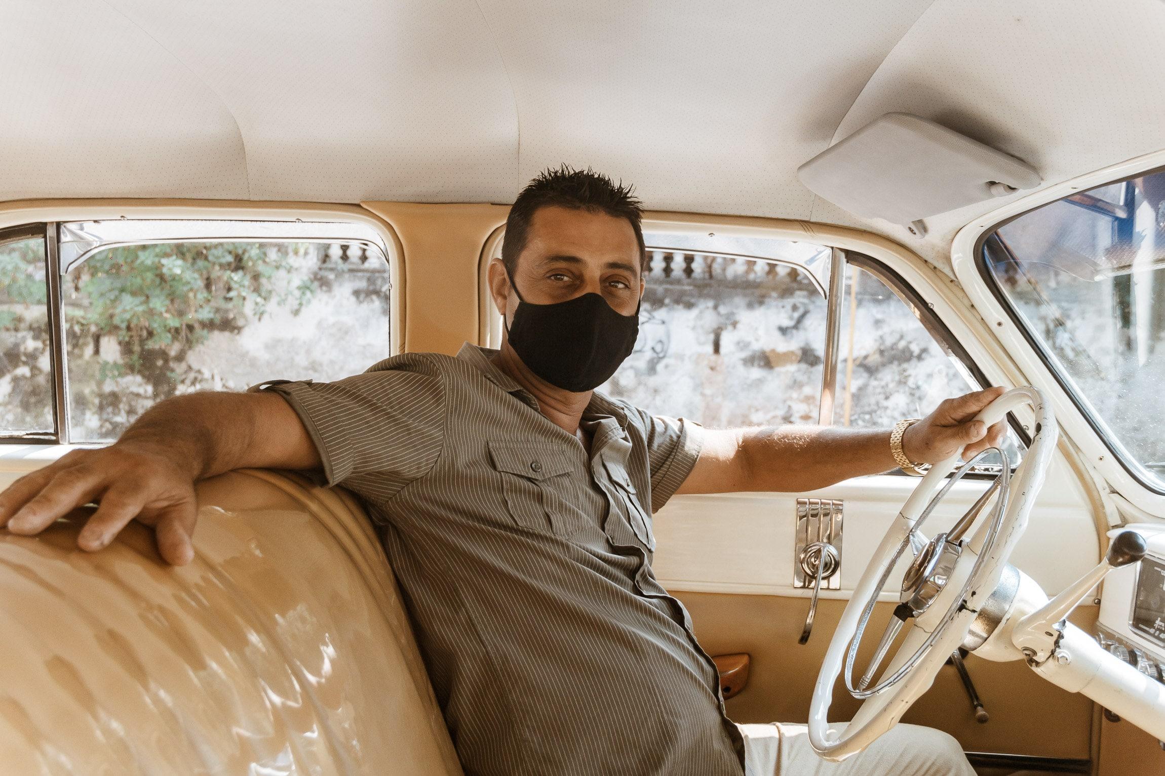 Chauffeur mit Maske im Oldtimer