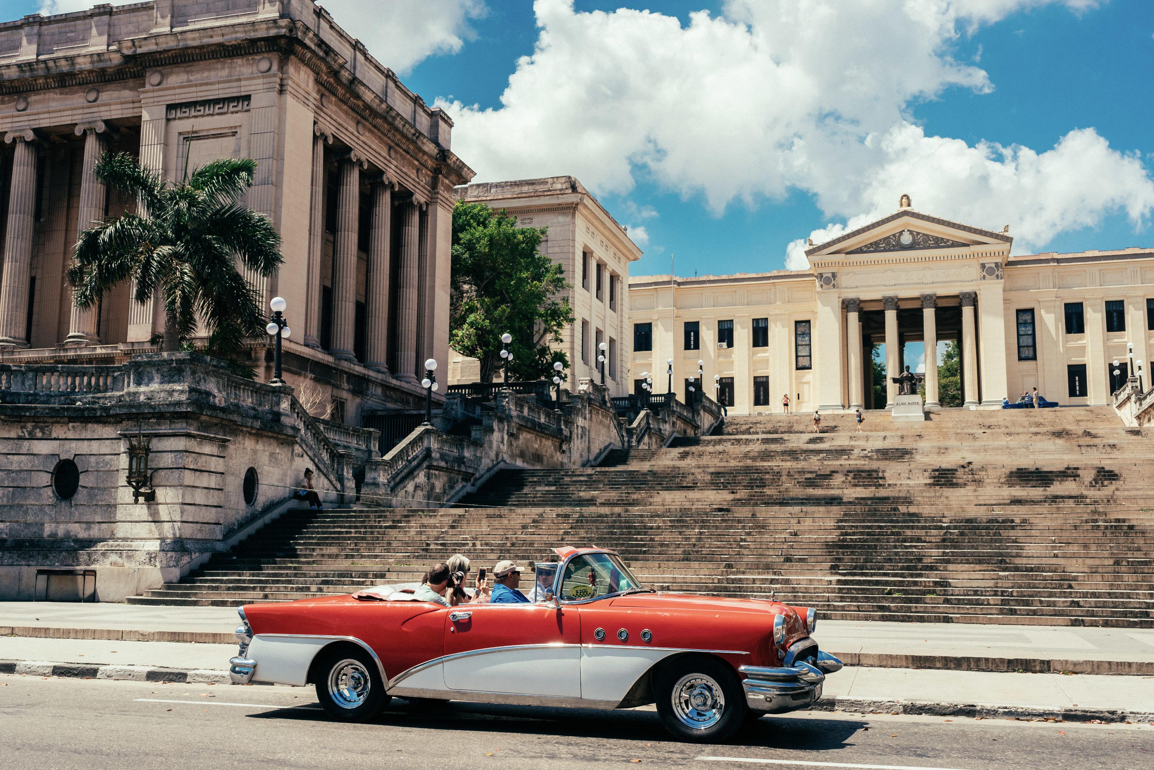 Ein Oldtimer steht vor der Universität Havannas