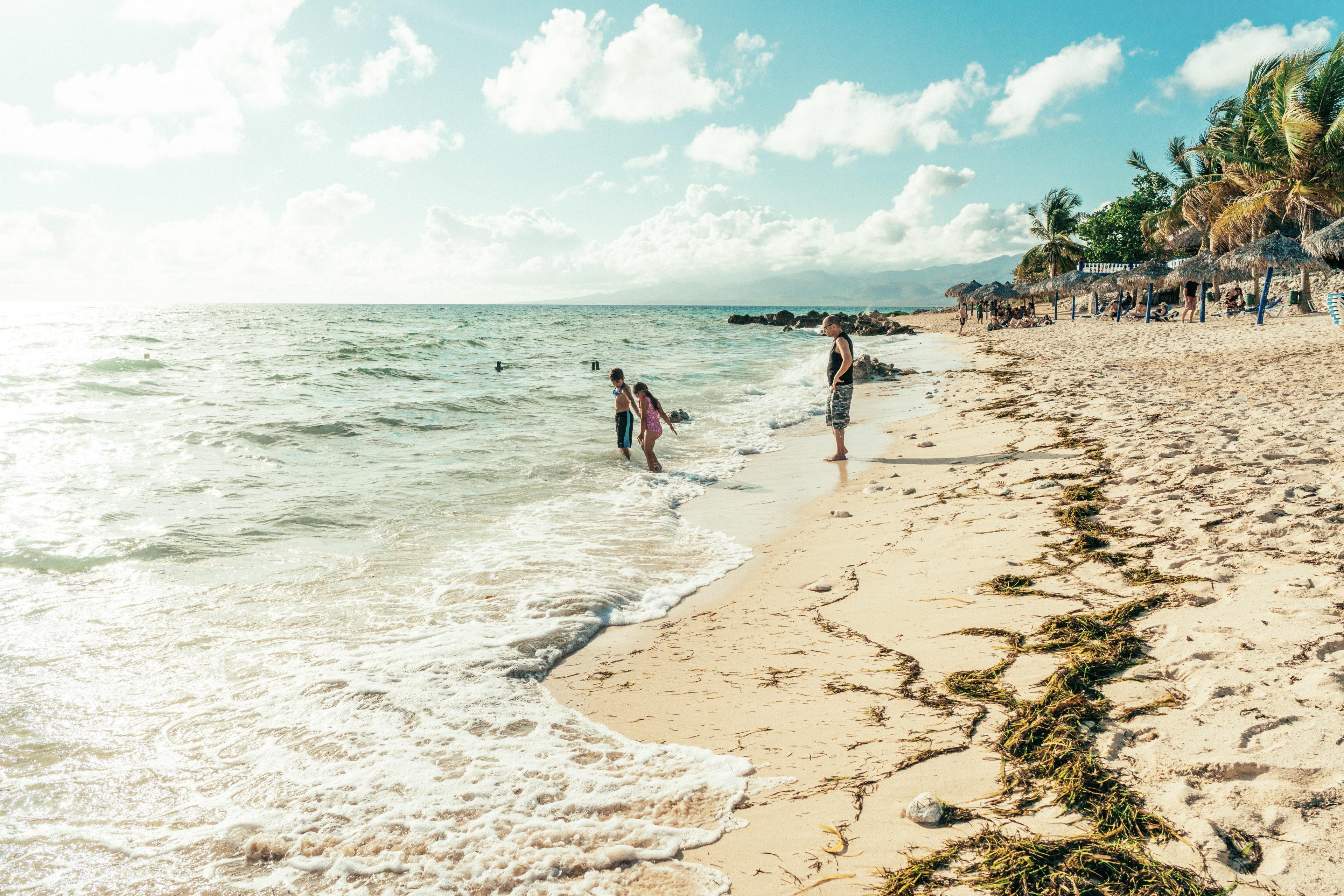 Menschen entspannen an einem weißen Strand in Kuba