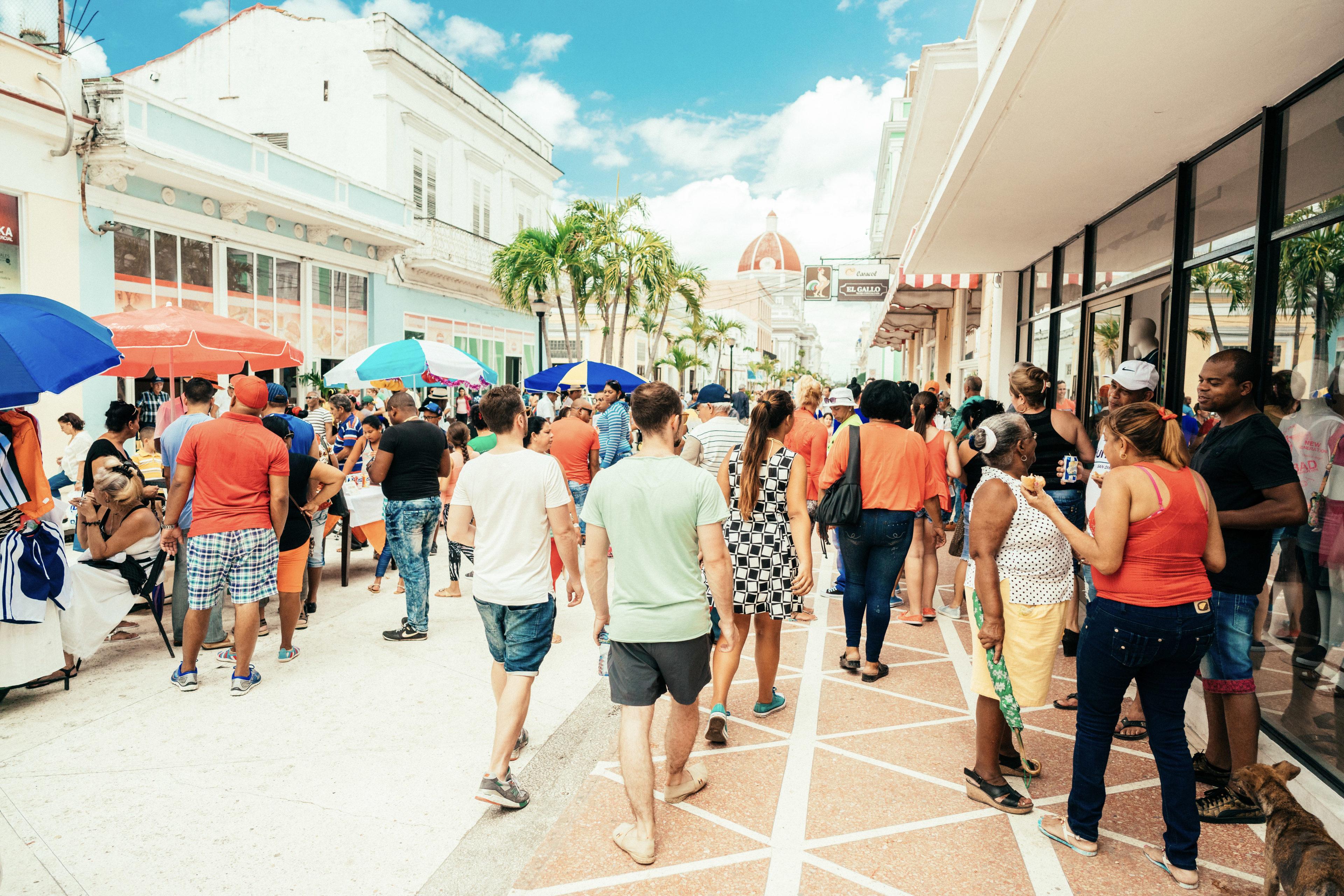 Touristen spazieren über einen Wochenmarkt in Kuba