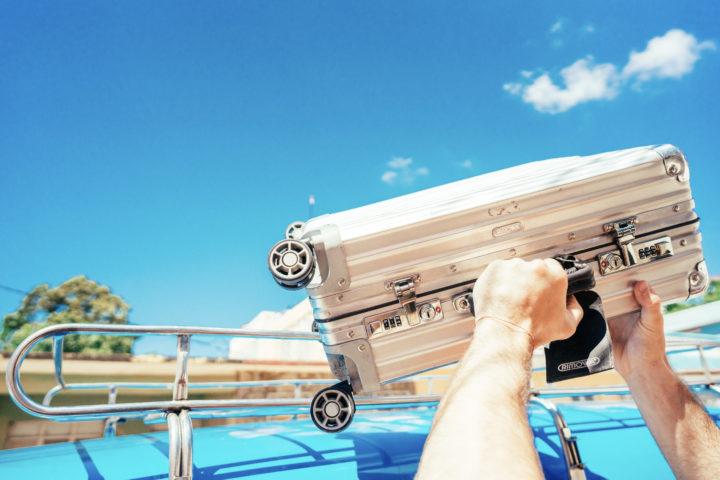 Ein Kuba-Reisender holt seinen Koffer vom Dach des Oldtimers in Kuba